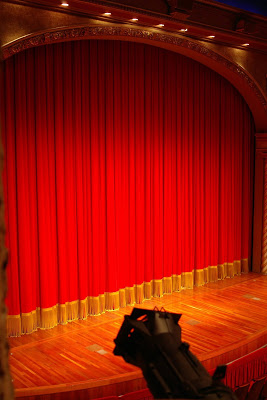 closed red curtain blocking a stage's contents
