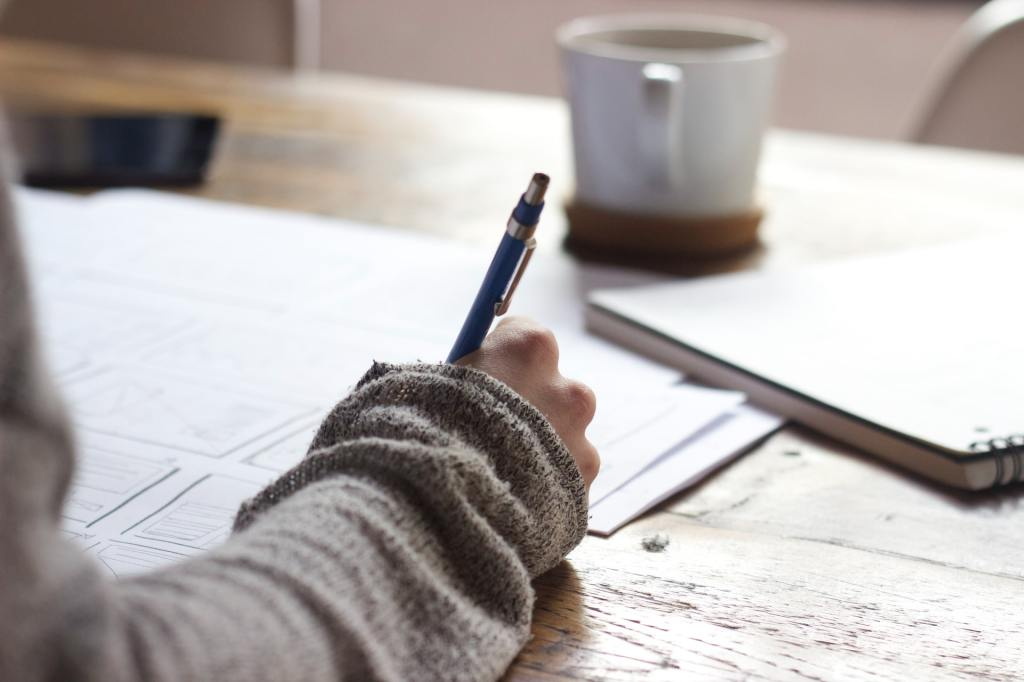 image of person writing at a table